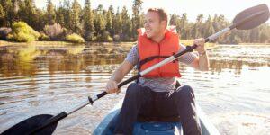 man-wearing-life-preserver-rowing-kayak-on-lake.jpg